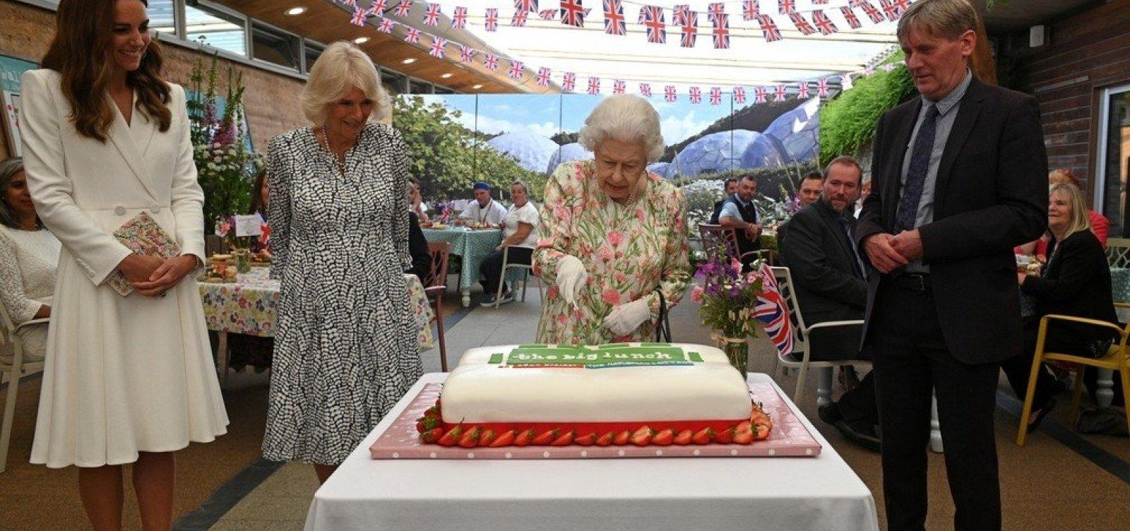 Rainha Elizabeth II usa uma espada para cortar um bolo em evento do G7